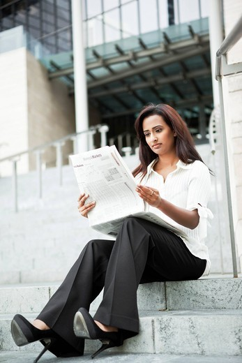 Indian businesswoman reading newspaper outdoors : Stock Photo