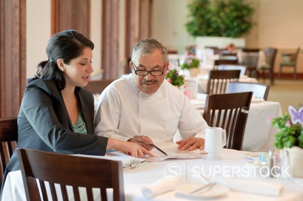 Stock Photo: 1589R-149328 Hispanic business owner talking to restaurant chef
