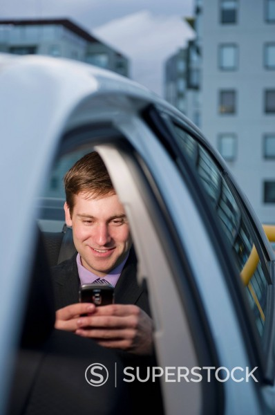 Stock Photo: 1589R-149369 Caucasian businessman using cell phone in back seat of car