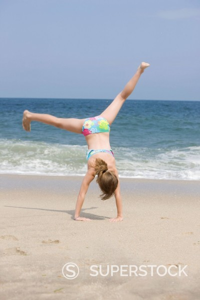 Stock Photo: 1589R-149419 Caucasian girl doing cartwheel on beach