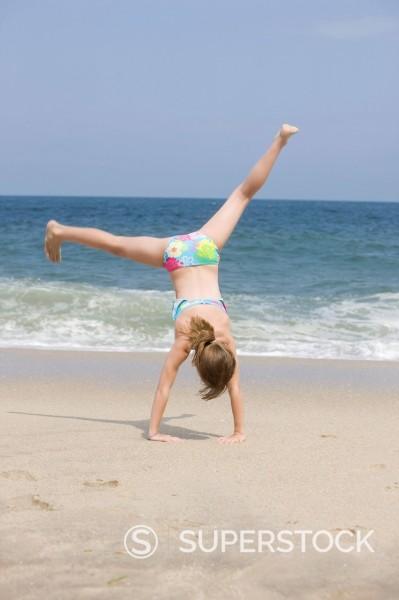 Caucasian girl doing cartwheel on beach : Stock Photo