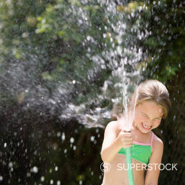 Stock Photo: 1589R-149423 Grinning girl squirting water