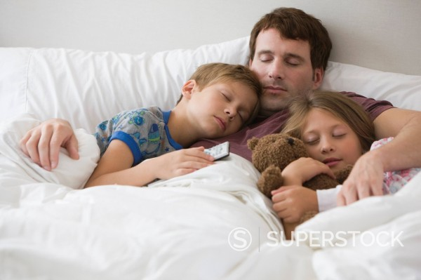 Caucasian father and children sleeping in bed together : Stock Photo