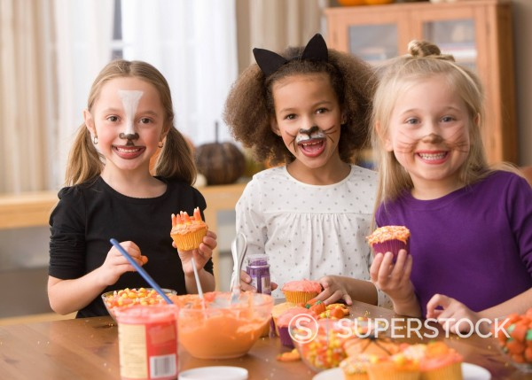 Stock Photo: 1589R-149516 Girls in Halloween costumes decorating cupcakes