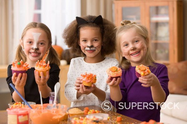Stock Photo: 1589R-149520 Girls in Halloween costumes decorating cupcakes