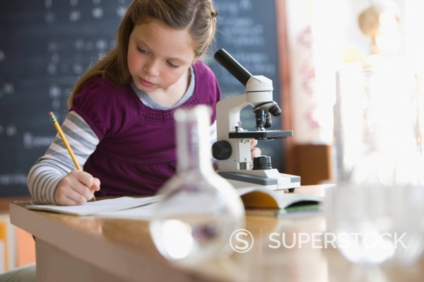 Caucasian girl looking into classroom microscope : Stock Photo