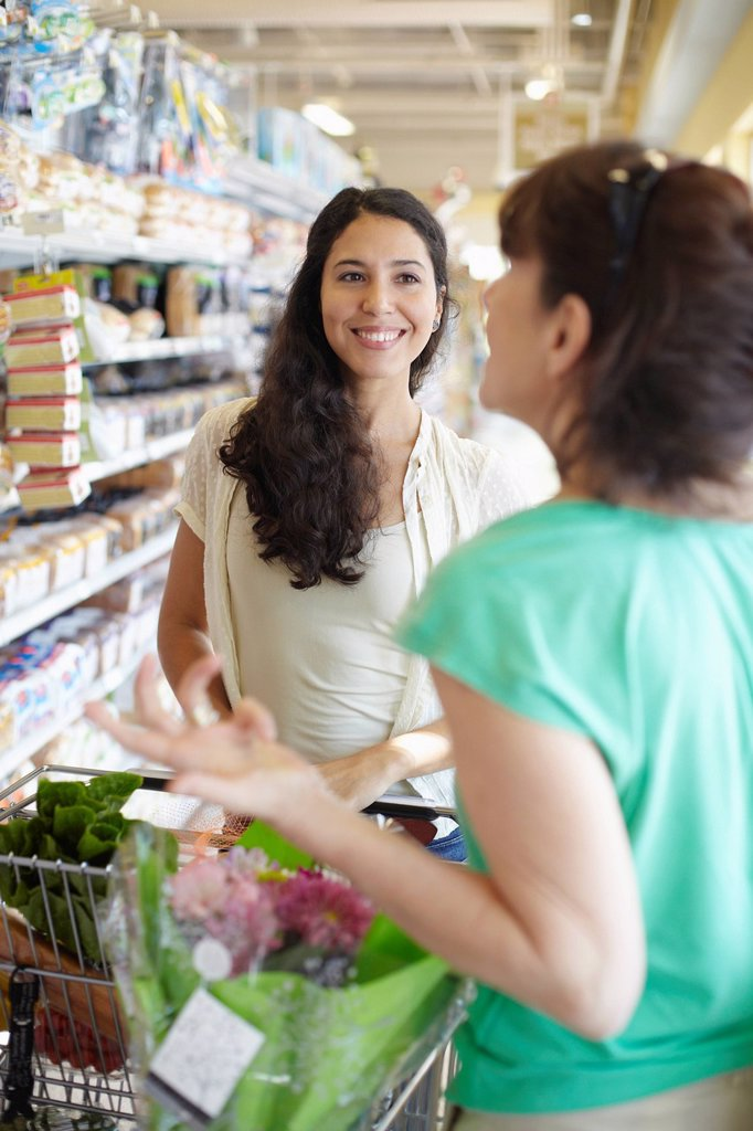Women talking together in grocery store : Stock Photo