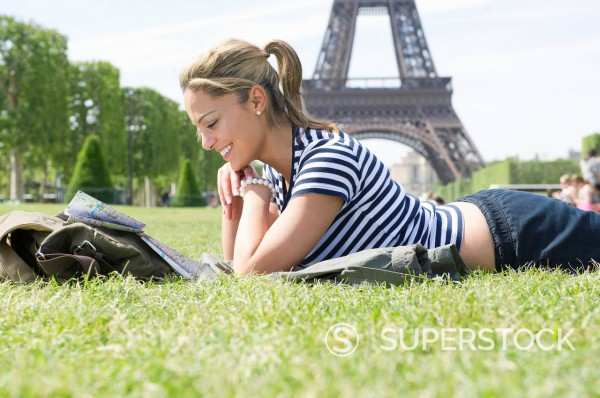 Stock Photo: 1589R-149768 Hispanic woman looking at map in park near Eiffel Tower
