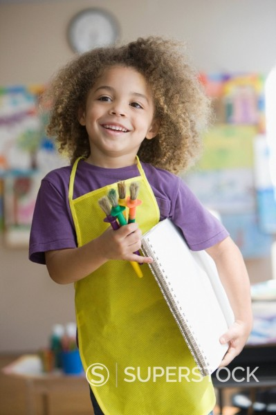 Mixed race boy standing in art class : Stock Photo