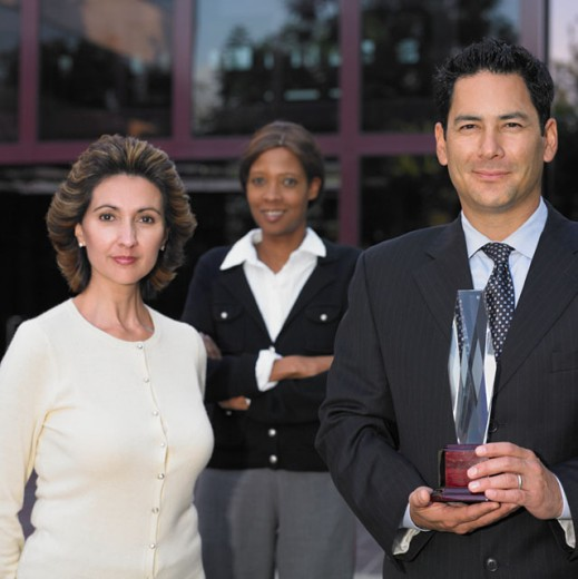 Stock Photo: 1589R-14994 Businesspeople posing for the camera with a glass trophy
