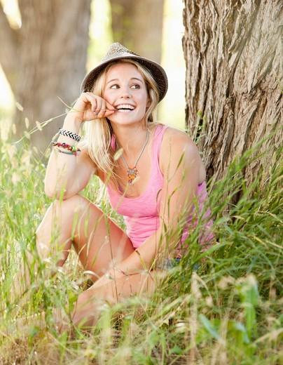 Caucasian woman sitting in grass : Stock Photo