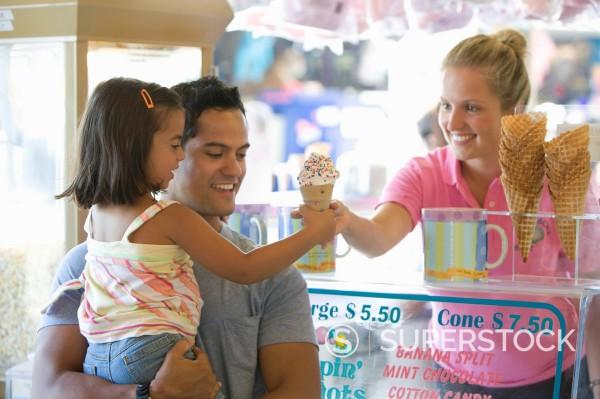 Waitress handing girl ice cream cone : Stock Photo