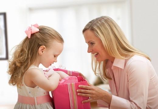 Caucasian mother giving daughter a gift : Stock Photo