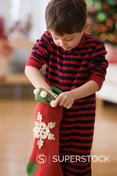 Stock Photo: 1589R-150584 Caucasian boy looking in Christmas stocking
