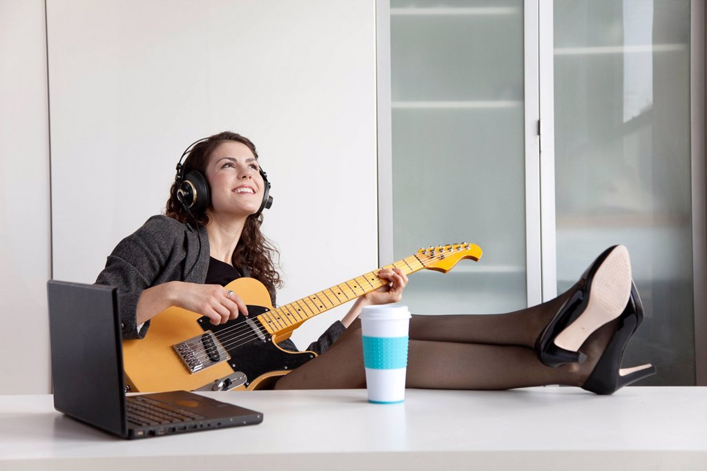 Businesswoman playing guitar at desk : Stock Photo