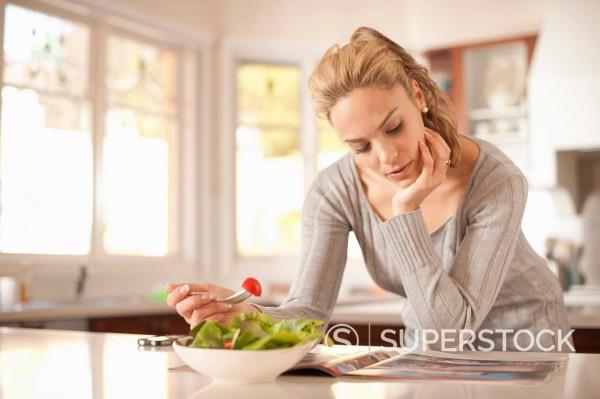 Hispanic woman eating salad and reading magazine : Stock Photo