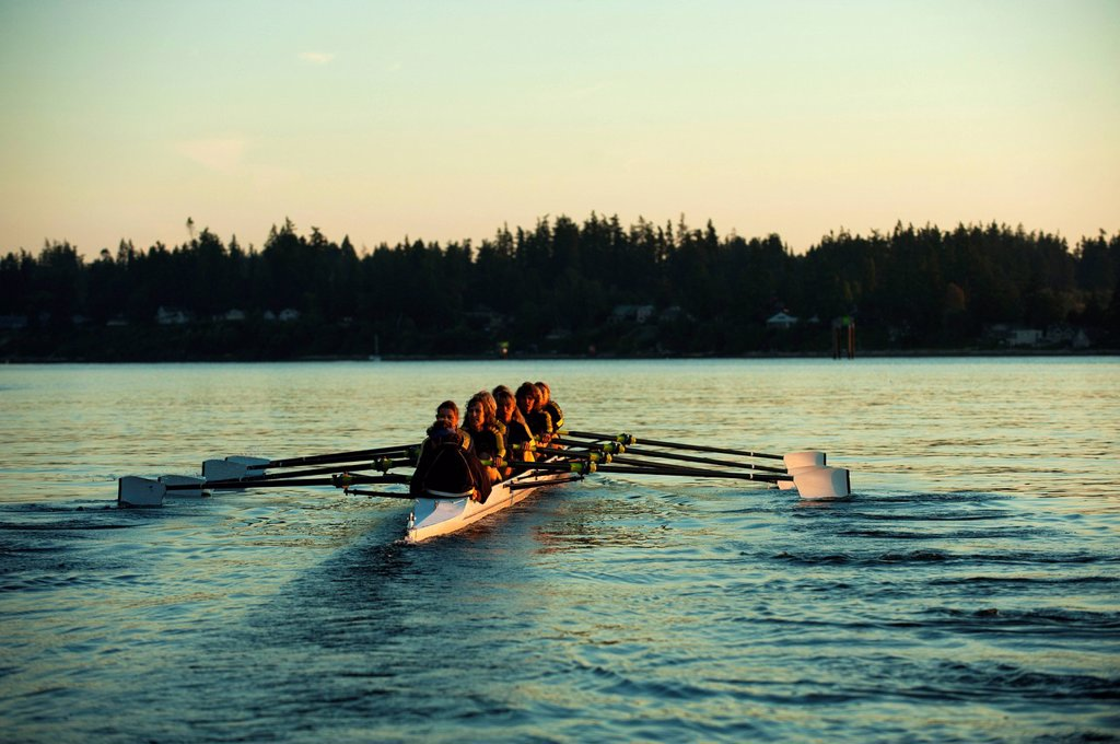 Team rowing boat in bay : Stock Photo