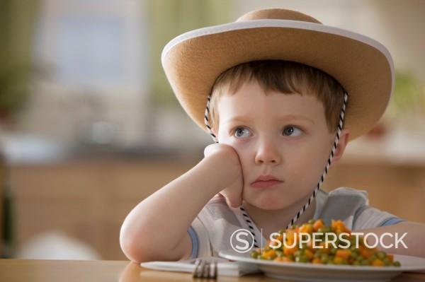 Stock Photo: 1589R-151299 Unhappy Caucasian boy sitting at dinner table