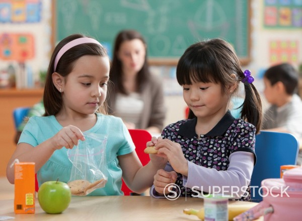 Girls eating lunch together in classroom : Stock Photo