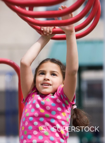 Hispanic girl playing on playground structure : Stock Photo