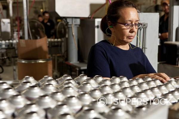 Hispanic woman working on assembly line : Stock Photo