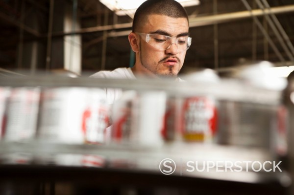 Hispanic man working on assembly line : Stock Photo