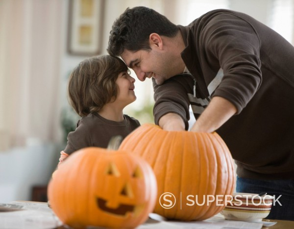 Stock Photo: 1589R-151422 Mixed race father and son carving Halloween pumpkins