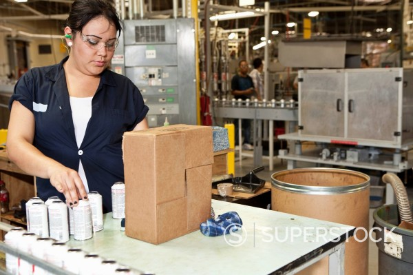 Hispanic worker packing boxes in factory : Stock Photo