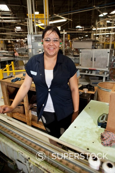 Hispanic woman working on assembly line : Stock Photo