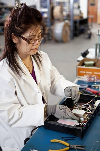 Asian woman working in electronics factory : Stock Photo