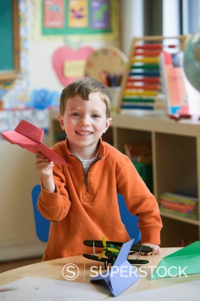 Stock Photo: 1589R-151486 Caucasian boy making paper airplane in classroom