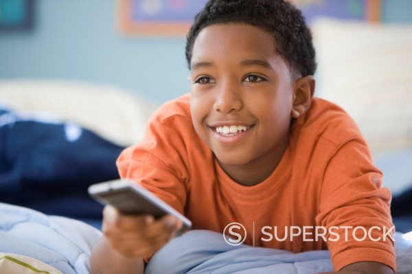 Stock Photo: 1589R-151562 Mixed race boy changing channel with remote control