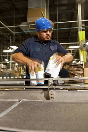 Hispanic worker holding cans on assembly line : Stock Photo