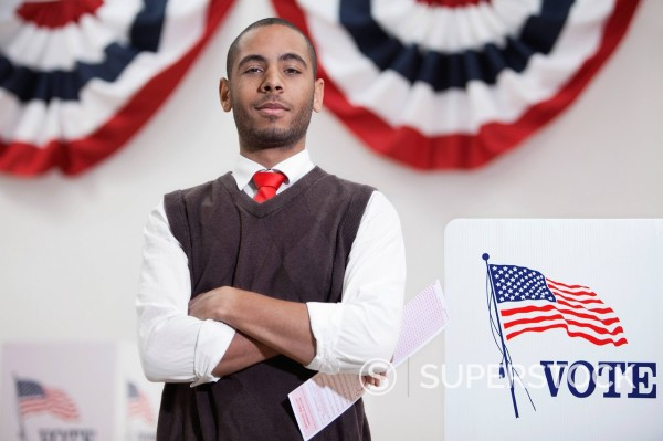 Stock Photo: 1589R-151758 Hispanic voter voting in polling place