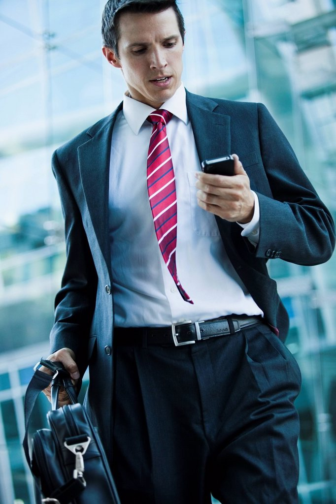 Stock Photo: 1589R-151799 Caucasian businessman looking at cell phone outdoors