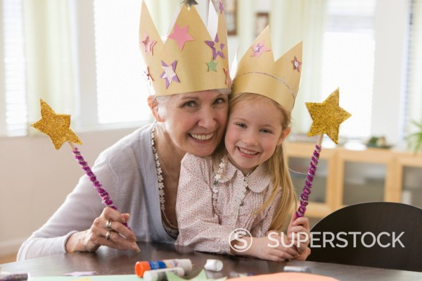Caucasian grandmother and granddaughter doing arts and crafts together : Stock Photo