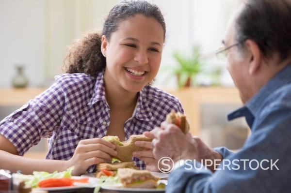 Hispanic girl and grandfather making sandwich : Stock Photo