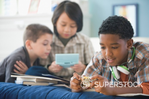 Stock Photo: 1589R-152010 Boys playing video games and listening to music