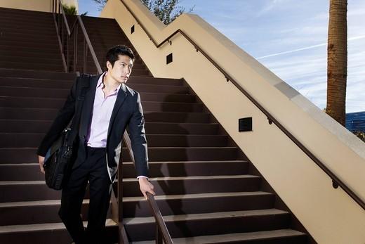 Asian businessman descending staircase : Stock Photo