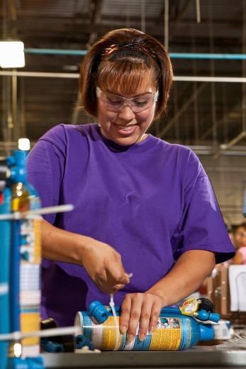 Hispanic worker assembling bottle in factory : Stock Photo