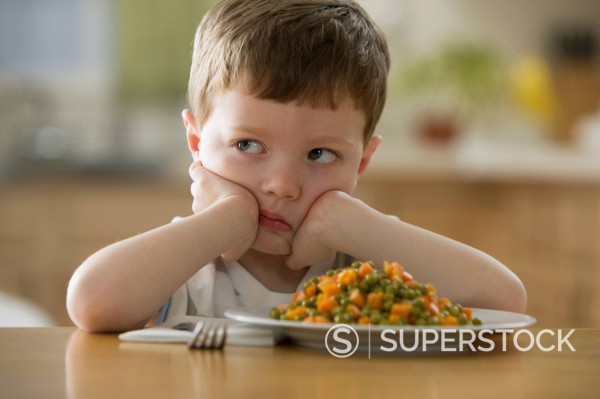 Stock Photo: 1589R-152210 Unhappy Caucasian boy sitting at dinner table