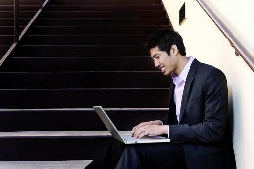 Asian businessman sitting on steps using laptop : Stock Photo