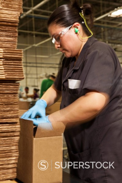 Hispanic woman packing boxes in factory : Stock Photo
