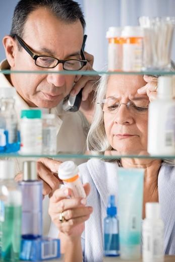 Hispanic couple in bathroom checking prescription : Stock Photo