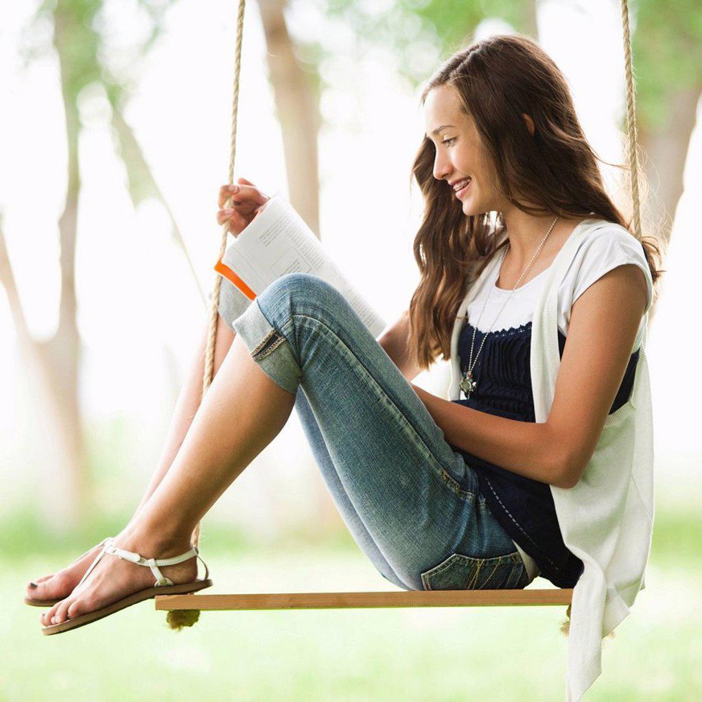 Caucasian girl reading book on swing : Stock Photo