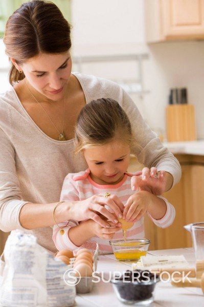 Caucasian mother and daughter baking together : Stock Photo
