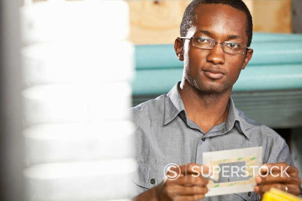 Black man working in electronics factory : Stock Photo