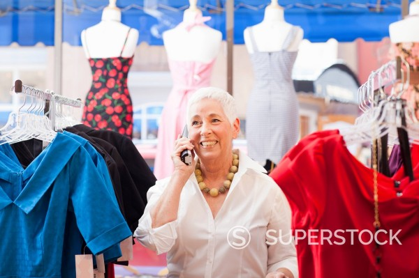 Stock Photo: 1589R-152467 Caucasian woman using phone in dress shop