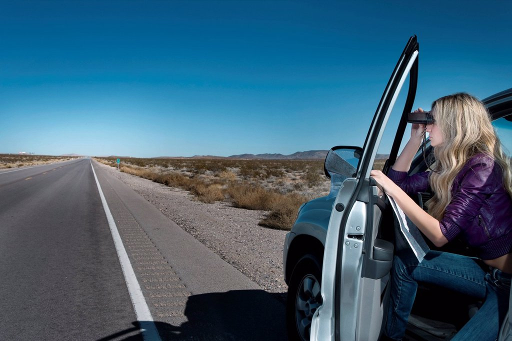 Stock Photo: 1589R-152527 Caucasian woman parked on roadside using binoculars
