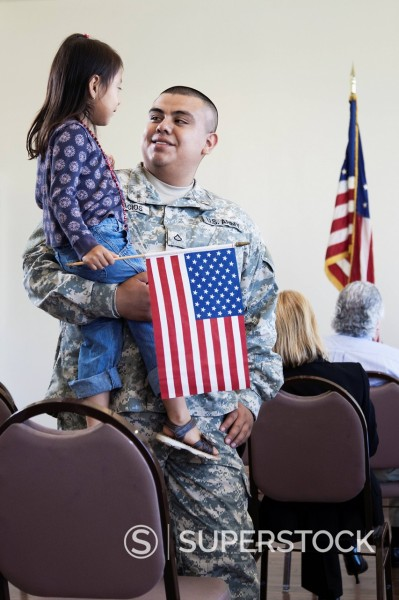 Hispanic soldier holding daughter at political gathering : Stock Photo
